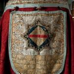 Capa pluvial d'Arnau de Vilalba<br /> S. XV <br /> Domàs i seda, brodat.<br /> 135 x 170<br /> Núm. Inv. 119<br /> Caputxa amb brodats de l'escut de l'abat Arnau de Vilalba.